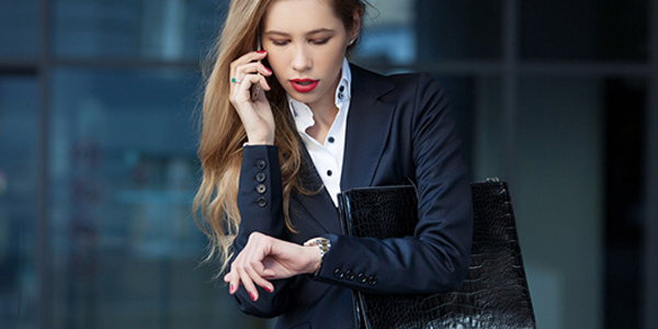 Woman with long hair in suit talking on mobile phone and looking at watch on her wrist