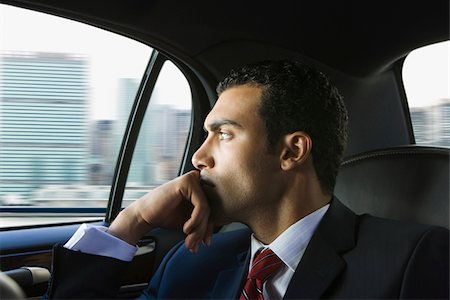Male passenger in vehicle gazing out the window