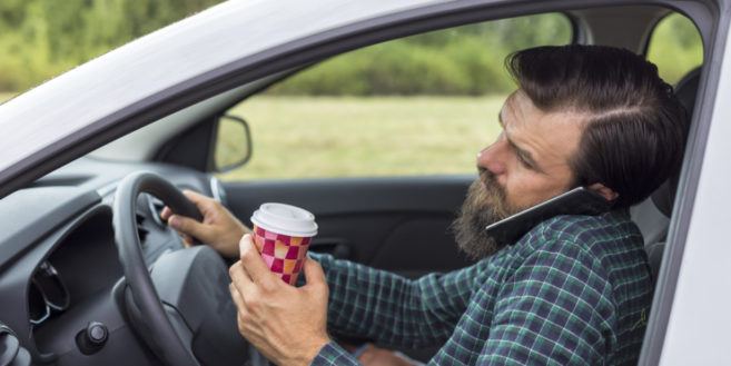 Man driving car holding coffee and talking on the phone