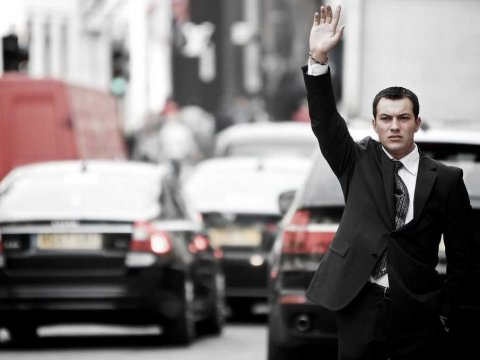 Man in black suit trying to hail a ride in busy street